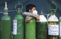A youth rests on his empty oxygen cylinder waiting for a refill shop to open in the San Juan de Lurigancho neighborhood of Lima, Peru, on Feb. 22, 2021. (AP Photo/Martin Mejia)
