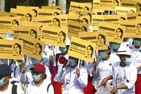 Medicals students display images of deposed Myanmar leader Aung San Suu Kyi during a street march in Mandalay, Myanmar, on Feb. 26, 2021. (AP Photo)