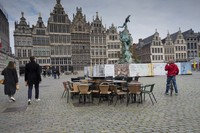 In this Oct. 20, 2020 file photo, people walk by chairs and tables of an empty terrace in the historical center of Antwerp, Belgium. (AP Photo/Virginia Mayo)