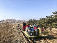 In this image taken from a video released by Russian Foreign Ministry Press Service on Feb. 25, 2021, a group of Russian diplomats push hand-pushed rail trolley with their children and suitcases to the border with Russia. (Russian Foreign Ministry Press Service via AP)