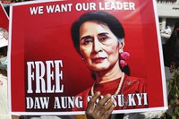 "A poster with an image of deposed Myanmar leader Aung San Suu Kyi and a sign that reads ""We Want our Leader. Free Daw Aung San Suu Kyi"" is held by an anti-coup protester during a rally near the Mandalay Railway Station in Mandalay, Myanmar, on Feb. 22, 2021. (AP Photo)"