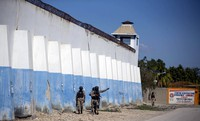 National police officers search for inmates on the perimeters of the Croix-des-Bouquets Civil Prison in Port-au-Prince, Haiti, on Feb. 25, 2021. (AP Photo/Dieu Nalio Chery)