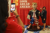 A woman takes a photo with a golden Donald Trump statue at the Conservative Political Action (CPAC) conference on Feb. 26, 2021, in Orlando, Florida. (Sam Thomas/Orlando Sentinel via AP)