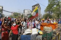 In this image made from video, anti-coup protesters shout at police in Yangon, Myanmar, on Feb. 27, 2021. (AP Photo)