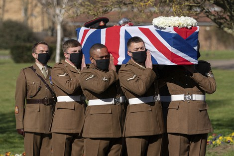 The coffin of Captain Sir Tom Moore is carried by members of the Armed Forces during his funeral, at Bedford Crematorium, in Bedford, England, Saturday, Feb. 27, 2021.