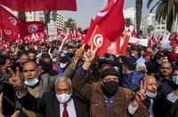 Supporters of the islamist Ennada party march with Tunisian flags during a rally in Tunis, Tunisia, Saturday, Feb. 27, 2021. (AP Photo/Hassene Dridi)