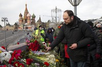 Vladimir Kara-Murza, Russian opposition activist lays flowers near the place where Russian opposition leader Boris Nemtsov was gunned down, in Moscow, Russia, Saturday, Feb. 27, 2021. (AP Photo/Alexander Zemlianichenko)