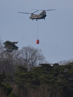 A Ground Self-Defense helicopter carries a bucket of water to extinguish wildfire in Ashikaga, Tochigi Prefecture, on March 1, 2021. (Mainichi/Yuzuru Ota)