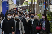 People wearing protective masks to help curb the spread of the coronavirus walk along a sidewalk in a shopping district on Sunday, Feb. 28, 2021, in Tokyo. (AP Photo/Kiichiro Sato)