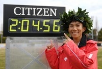 Kengo Suzuki smiles for photos next to the time board showing his record in the 76th Lake Biwa Mainichi Marathon, at Ojiyama Stadium in Otsu, on Feb. 28, 2021. (Mainichi/Rei Kubo)