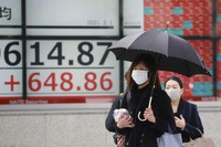 People walk by an electronic stock board of a securities firm in Tokyo, Monday, March 1, 2021. (AP Photo/Koji Sasahara)