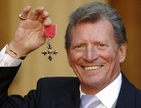 In this March 7, 2007 file photo, actor Johnny Briggs poses for the media after collecting an MBE from Queen Elizabeth II at Buckingham Palace in London. (Fiona Hanson/PA via AP)
