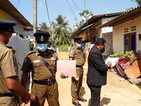 Sri Lankan magistrate Wasantha Ramanayake, right and police officers inspect outside a house where a nine-year-old girl was canned to death in Delgoda, Sri Lanka, on Feb.28, 2021. (AP Photo/ Sudath Pubudu Keerthi)