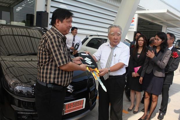 タイのディーラーで新工場から出荷されたスイフトのキーを渡す鈴木修会長兼社長(2012年11月)