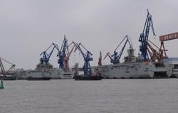 2隻同時に建造が進む強襲揚陸艦「075型」。平らな甲板、船尾の開口部が特徴だ=中国上海市で2021年2月17日、河津啓介撮影