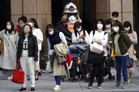 People wearing masks to help curb the spread of the coronavirus wait for a traffic light at an intersection on Monday, March 1, 2021, in Tokyo. (AP Photo/Eugene Hoshiko)