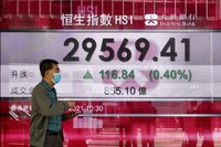 A man walks past a bank's electronic board showing the Hong Kong share index at Hong Kong Stock Exchange in Hong Kong on March 2, 2021. (AP Photo/Vincent Yu)