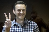 In this Feb. 20, 2021 file photo, Russian opposition leader Alexei Navalny gestures as he stands behind a grass of the cage in the Babuskinsky District Court in Moscow, Russia. (AP Photo/Alexander Zemlianichenko)