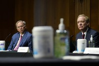 Dr. Eric E. Schmidt, co-founder of Schmidt Futures, left, and Brad Smith, president of Microsoft Corporation, right, listens on Capitol Hill in Washington on Feb. 23, 2021, during a hearing on emerging technologies and their impact on national security. (AP Photo/Susan Walsh)