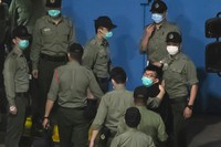 Joshua Wong, right, one of the 47 pro-democracy Hong Kong activists, is escorted by Correctional Services officers to prison in Hong Kong on March 2, 2021. (AP Photo/Kin Cheung)