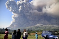 People watch as Mount Sinabung spews volcanic material during an eruption in Karo, North Sumatra, Indonesia, on March 2, 2021.  (AP Photo)