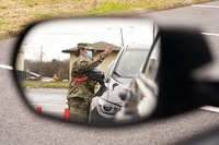 A National Guard soldier directing drivers is reflected in the mirror of a car waiting in a COVID-19 vaccination line Feb. 26, 2021, in Shelbyville, Tenn. (AP Photo/Mark Humphrey)