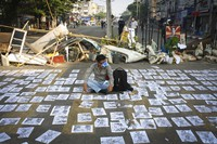 A protester wearing a gas mask sits on a blocked road in Yangon, Myanmar, on March 2, 2021. (AP Photo)