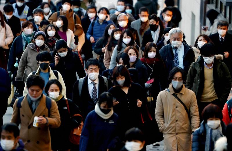 Orang-orang yang memakai topeng dan menuju ke stasiun dengan cepat = Diambil oleh Yuki Miyatake pada tanggal 7 Januari 2021 di Shinjuku-ku, Tokyo