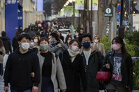 People wearing protective masks to help curb the spread of the coronavirus walk along a sidewalk in a Tokyo shopping district on Feb. 28, 2021. (AP Photo/Kiichiro Sato)