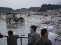 Evacuees are seen looking at the flooded city area from the rooftop of the Kesennuma Chuo Kominkan community hall in this photo provided by Naoko Utsumi.