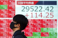 A man wearing a protective mask walks past an electronic stock board showing Japan's Nikkei 225 index at a securities firm on March 3, 2021, in Tokyo. (AP Photo/Eugene Hoshiko)