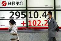 People wearing protective masks walk in front of an electronic stock board showing Japan's Nikkei 225 index at a securities firm on March 3, 2021, in Tokyo. (AP Photo/Eugene Hoshiko)