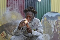"In this Aug. 28, 2014 file photo, legalization advocate and reggae legend Bunny Wailer smokes a pipe stuffed with marijuana during a ""reasoning"" session in a yard in Kingston, Jamaica. (AP Photo/David McFadden)"