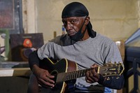 "Bluesman Jimmy ""Duck"" Holmes plays a quick ditty at the Blue Front Cafe in Bentonia, Miss., on Jan. 21, 2021. Holmes' ninth album, ""Cypress Grove,"" has earned a Grammy nomination for the Best Traditional Blues Album. (AP Photo/Rogelio V. Solis)"