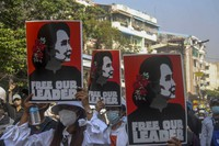 Anti-coup protesters display pictures of deposed Myanmar leader Aung San Suu Kyi in Yangon, Myanmar, on March 2, 2021. (AP Photo)