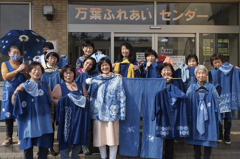 In this image from video, members of Japan Blue hold up their dyed clothes and pose for a photo in front of a community center which was used as an evacuation center when the massive earthquake hit the area in 2011, in Minamisoma, Fukushima Prefecture, northeastern Japan, on Feb. 20, 2021. (AP Photo/Chisato Tanaka)