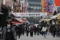 People wearing face masks walk through a market in Seoul, South Korea, on March 4, 2021. (AP Photo/Ahn Young-joon)