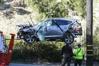 In this Feb. 23, 2021, file photo, a crane is used to lift a vehicle following a rollover accident involving golfer Tiger Woods, in the Rancho Palos Verdes suburb of Los Angeles. (AP Photo/Ringo H.W. Chiu)