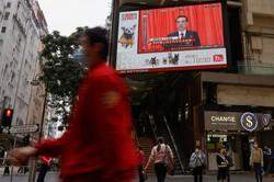 街頭の大型モニターに映し出された全人代で政府活動報告をする李克強首相=香港で5日、ロイター