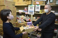 Pasona Inc.'s Shiga branch employee Anna Takai, left, is seen handing over a box full of food items collected at the office to Food Bank Biwako Chairman Toshihiro Soda at the association's food storage in the city of Moriyama, Shiga Prefecture, on March 1, 2021. (Mainichi/Yusuke Konishi)