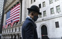 In this Nov. 16, 2020 file photo, a man wearing a mask passes the New York Stock Exchange in New York. (AP Photo/Mark Lennihan)