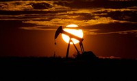 In this April 8, 2020, file photo, the sun sets behind an idle pump jack near Karnes City, USA. (AP Photo/Eric Gay)