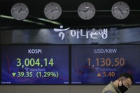 A currency trader talks near screens showing the Korea Composite Stock Price Index (KOSPI), left, and the foreign exchange rate between the U.S. dollar and South Korean won at the foreign exchange dealing room in Seoul, South Korea, on March 5, 2021. (AP Photo/Lee Jin-man)