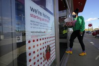 In this Sept. 30, 2020 file photo, a passerby walks past a hiring sign while entering a Target store in Westwood, Massachusetts. (AP Photo/Steven Senne)