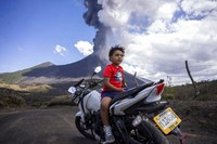 A child sits on a motorcycle as the Pacaya volcano erupts in the background, viewed from San Vicente Pacaya, Guatemala, on March 3, 2021. (AP Photo/Santiago Billy )