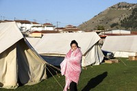 A girl standing outside a tent, uses a blanket to stay warm after an earthquake in Damasi village, central Greece, on March 4, 2021. (AP Photo/Vaggelis Kousioras)
