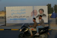 Iraqis put up a poster announcing the upcoming visit of the Pope Francis and a meeting with Grand Ayatollah Ali al-Sistan, a revered Shiite Muslim leader, right, in Najaf, Iraq, on March 4, 2021. (AP Photo/Anmar Khalil)