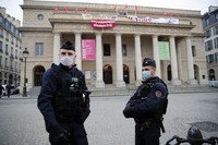 Police officers stand outside the occupied iconic Odeon theater on March 5, 2021, in Paris. (AP Photo/Francois Mori)