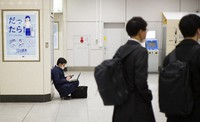 A man wearing a face mask looks at his cellphone while using a laptop at a train station in Tokyo on March 4, 2021. (AP Photo/Hiro Komae)