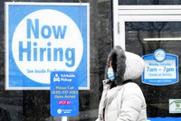 """In this Feb. 6, 2021, file photo, a woman walks past a """"Now Hiring"""" sign displayed at a CD One Price Cleaners in Schaumburg, Ill. (AP Photo/Nam Y. Huh)"""